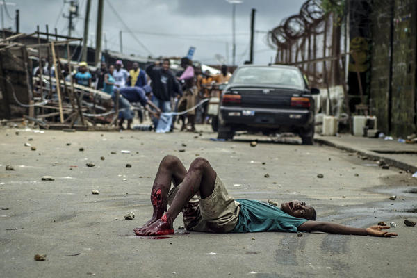 16-year-old Shacki <em>Kamara</em>, with a bullet wound in his leg, cries for help in between police and rioters in West Point.