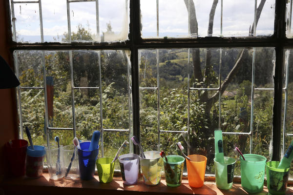 Students' toothbrushes and cups sit on a windowsill.