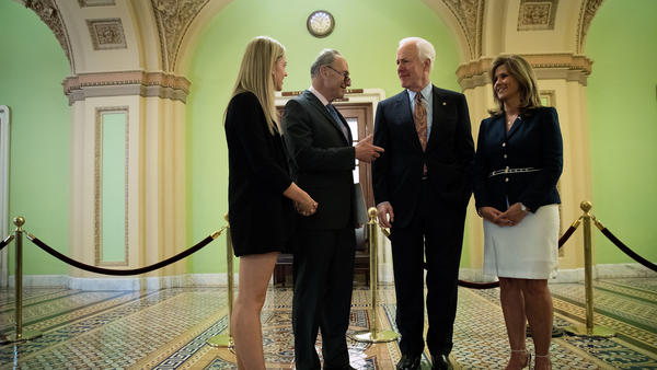 Sens. Chuck Schumer, D-N.Y., and John Cornyn, R-Texas, speak with Kaitlyn (left) and Terry Strada — whose husband, Thomas, died in the Sept. 11 attacks — after a May 17 news conference concerning the Justice Against Sponsors of Terrorism Act in Washington.