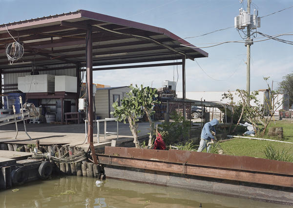 Lê's <em>November 9, Graffiti, New Orleans, Louisiana</em> shows three men gardening in a small plot of land next to the water.