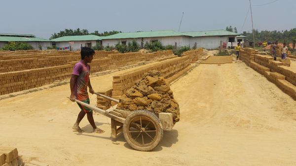 Workers at a brick factory toil through sweltering heat to shape, dry and bake bricks. The work is seasonal and labor-intensive. The manager says if he has openings, he'll give a job to anyone willing to do the work.