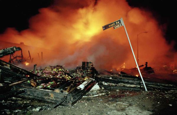 The remains of a commercial building smoulders as another building burns out of control behind the smoke in Los Angeles early on the morning of April 30, 1992.