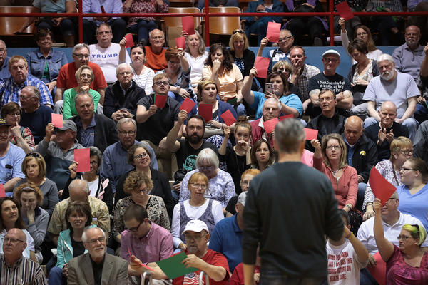 People attending Rep. Rod Blum's town hall event in Dubuque, Iowa, this week held up red sheets of paper to show disagreement with what the Republican congressman was saying and green to show they concurred. The GOP health care bill was a major concern of many.