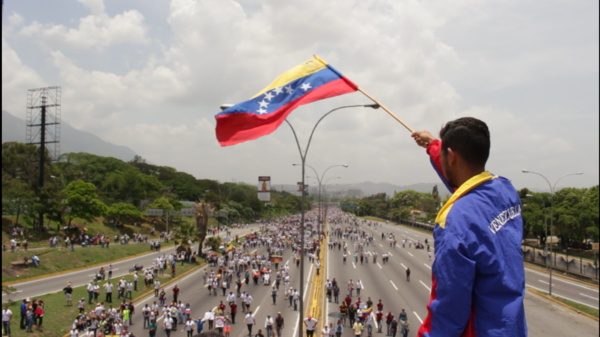 Wuilly Arteaga waves the Venezuelan flag as demonstrators gather below.