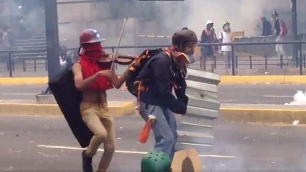 Wuilly Arteaga plays the violin as tear-gas canisters explode in Caracas, Venezuela.