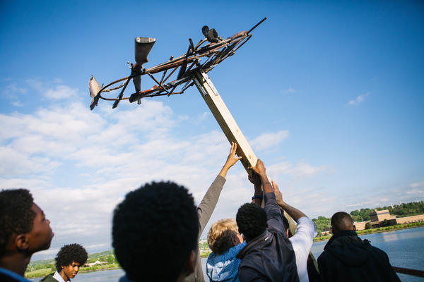 Students help raise the base of a new osprey nest, welded from parts including decommissioned firearms seized by the D.C. police.