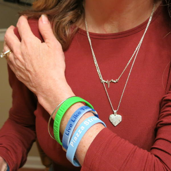 """Evelyn Piazza wears a heart-shaped pendant around her neck that has Timothy's thumbprint on it. """"It's like holding his hand when I rub my finger across the thumbprint. It's him. I'm wearing him,"""" she says."""