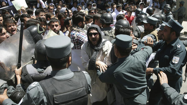 "Police forces struggle against protesters during a demonstration Friday in Kabul, Afghanistan. President Ashraf Ghani denounced the violence as partly caused by ""those who want to agitate and hurt public order."""