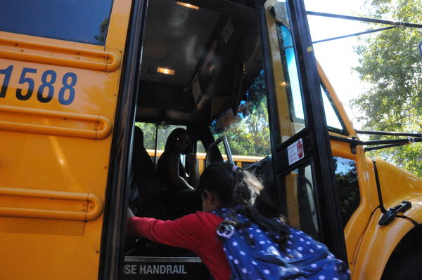 Wake County bus driver Auh-Murel Wright greets a student before the afternoon trip home. Wright is among many school-based employees who struggle to make ends meet on their current salaries.