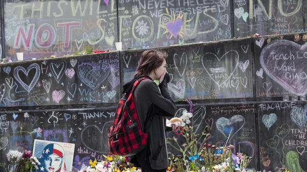 A woman looks at a memorial at the Hollywood Transit Center in Portland, Ore., on Thursday. Last week three men were stabbed, two fatally, after they stood up for two young women who were being harassed on a MAX train at the center.