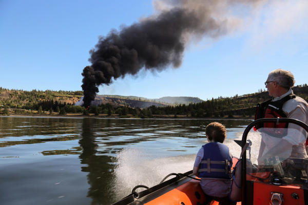 <p>Chris Hooper, right, of White Salmon watches the fire caused by a derailed oil train in Mosier, Oregon, near Hood River in the Columbia River Gorge on Friday, June 3, 2016.</p>