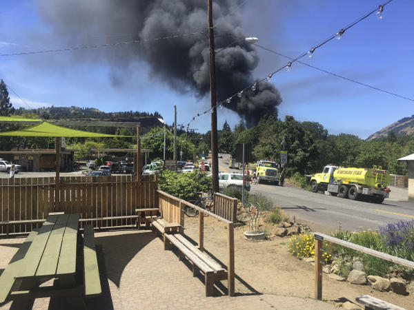 <p>In this photo provided by Silas Bleakley, a train towing cars full of oil sends up a plume of smoke after derailing Friday, June 3, 2016, near Mosier, Ore. The accident happened just after noon about 70 miles east of Portland. It involved eight cars filled with oil, and one was burning. Highway 84 was closed for a 23-mile stretch between The Dalles and Mosier and the radius for evacuations was a half-mile. </p>