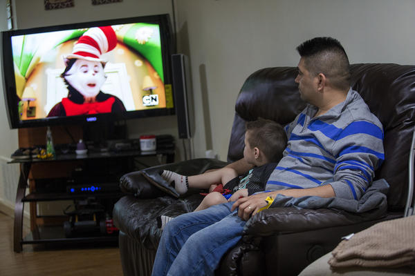 Jose Flores watches television with his young son. (Jesse Costa/WBUR)
