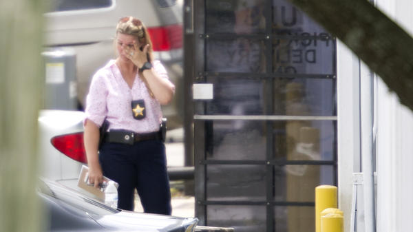 A law enforcement official wipes her eyes at the entrance to the scene of a workplace shooting near Orlando, Fla., on Monday. Authorities say the suspect was fired from the company in April and then returned and shot and killed five people before killing himself.