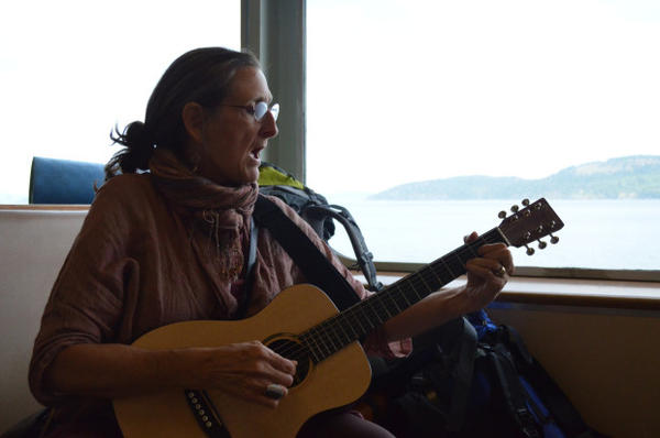 <p>Julienne Battalia, one of the pipeline protesters who traveled from Washington to British Columbia to join a march opposing expanding oil transport through the Salish Sea. She and others in her group sang about the sea, which is shared by Washington and BC, while taking a ferry ride to Victoria.</p>