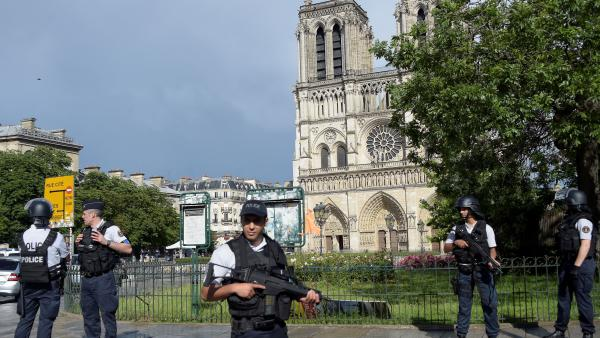 French police gather near the site of an attack near the entrance of Notre Dame Cathedral in Paris on Tuesday. Anti-terrorist prosecutors have opened an investigation after police shot and injured a man who had tried to attack officers with a hammer. One officer was slightly injured.