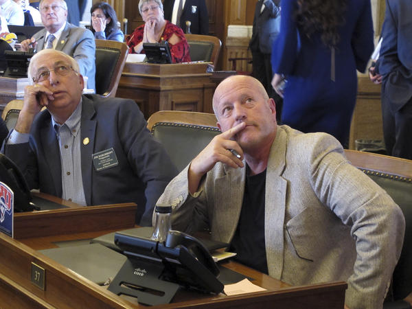 Kansas lawmakers watch an electronic voting board during votes on a bill to raise taxes and boost school funding at the Statehouse in Topeka, Kan.