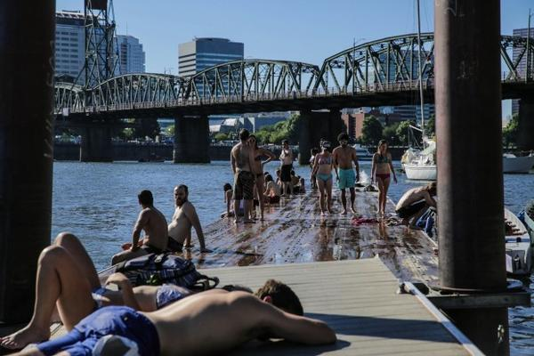 <p>Swimmers gather on a dock on the Willamette River in Portland.</p>