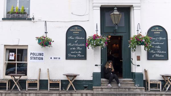 A woman sits outside the Anglesea Arms pub, set up as a polling station during Britain's general election, in London on Thursday.