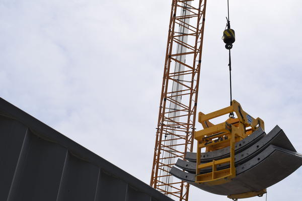 A crane lifts pieces to construct a new tunnel.