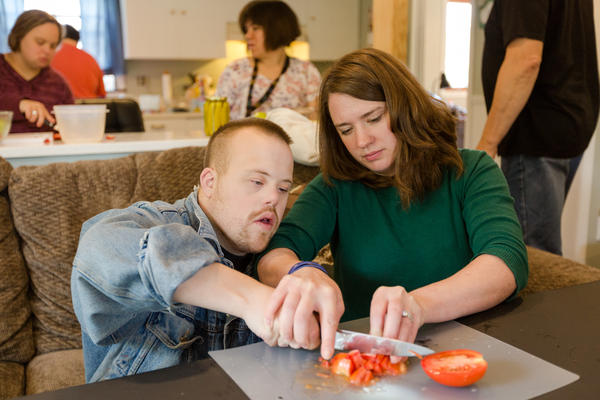 Justine Orr (right), program manager for Our Place Day Services, helps David Breuer chop tomatoes during a cooking class at the center north of Milwaukee. Nearly all the center's clients pay for services with funds from Medicaid.