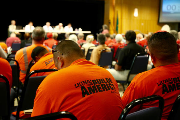 <p>Supporters of the oil terminal project included local labor unions, who wore orange T-shirts at the hearing. Opponents of the project dressed in red.</p>