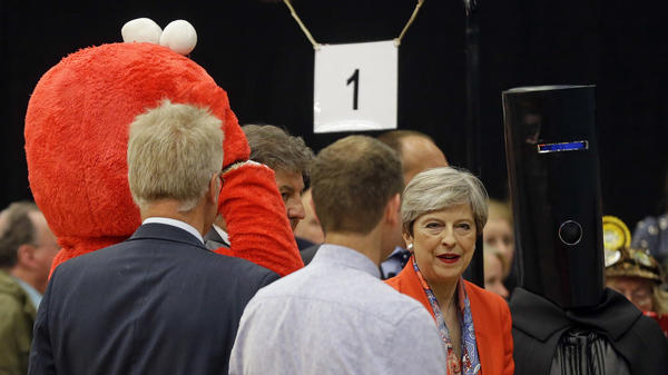 British Prime Minister Theresa May stands between Lord Buckethead (right) and Elmo, because — well, because sometimes democracy is weird.