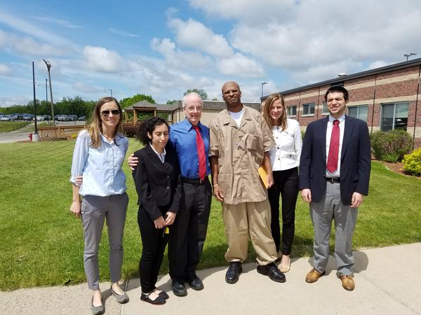 Desmond Ricks and members of the Michigan Innocence Clinic pose outside the prison where Ricks had been held since 1992.