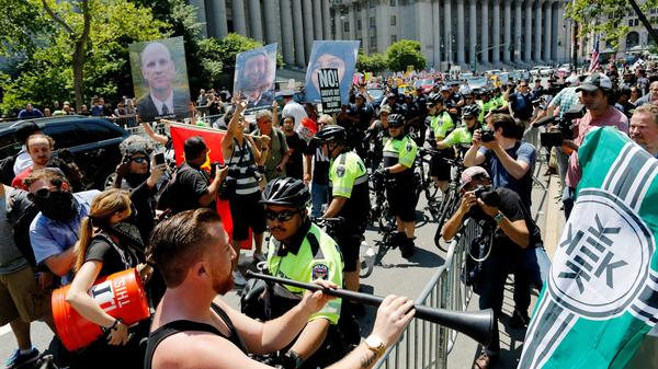 "NYPD officers try to separate counter-protesters and activists rallying for the ""March Against Sharia"" on Saturday in New York City."