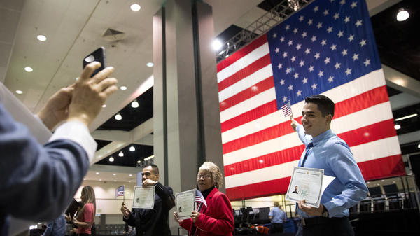 Immigrants pose with U.S citizenship certificates in front of a large U.S. flag after a naturalization ceremony at the Los Angeles Convention Center in February. A Supreme Court decision Monday will put the foreign-born children of unmarried American fathers on equal footing with those of unwed American mothers. That may mean longer waits for the latter, at least in the short term.