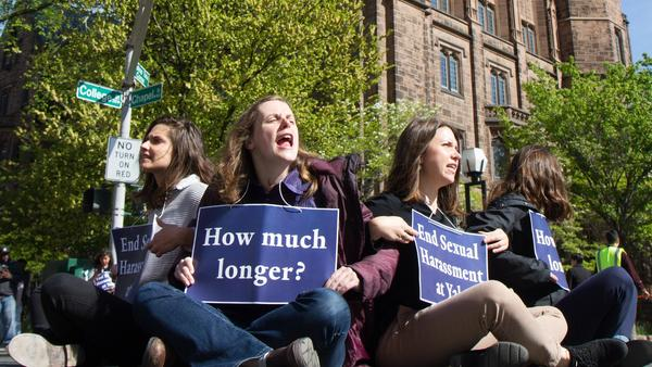 Yale graduate student instructors (from left) Kelly Goodman, Robin Canavan and Gwen Prowse block an intersection in downtown New Haven, Conn., on May 11, to protest what they say is the university's inaction on sexual harassment.