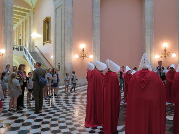 School children watch as Handmaid's Tale protestors gather