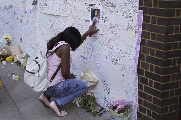 A woman touches a poster for 12-year-old Jessica Urbano on a tribute wall Friday after laying flowers on the side of a church next to the Grenfell Tower in London.