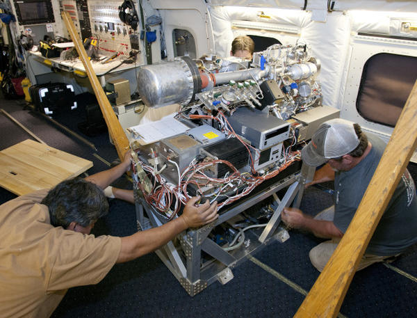 <p>Researchers work on instruments inside a specially outfitted plane.</p>