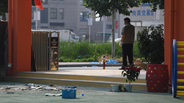 A security guard stands at the gate of the kindergarten in Xuzhou, where a blast killed at least seven people and injured dozens more on Thursday. Authorities say the cause was a bomb built by a man who died in the explosion.