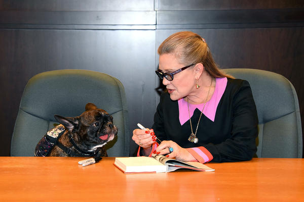 Carrie Fisher and her dog Gary Fisher sign copies of her new book <em>The Princess Diarist</em> at Barnes & Noble in Los Angeles in November 2016.