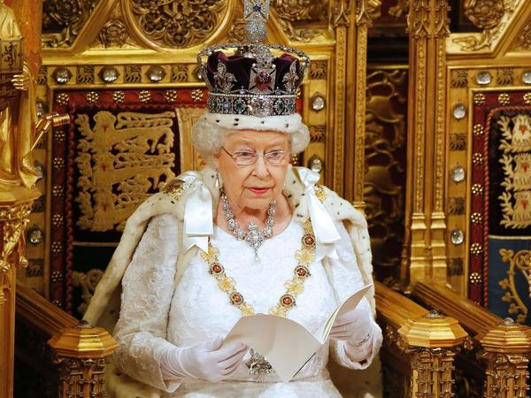 Britain's Queen Elizabeth II, draped in the royal robes, delivers the Queen's Speech during the State Opening of Parliament in central London, on May 18, 2016. She won't be wearing it when she gives her speech to Parliament this year, and NPR's Melissa Block will have to wait until 2018 for <em>all</em> the pageantry to return.