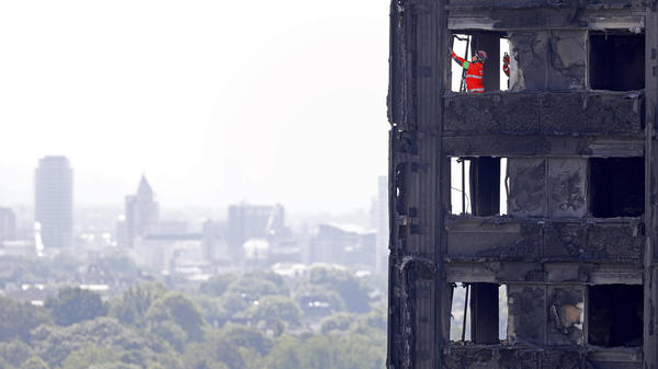 "Emergency service workers probe the remains of Grenfell Tower in London on Saturday. City police have announced 58 people remain missing and ""we assume likely to have died."""