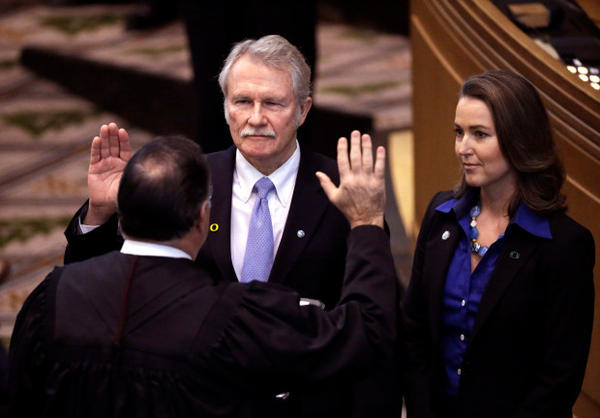 <p>Oregon Gov. John Kitzhaber, center, is joined by his fiancee, Cylvia Hayes, as he is sworn in for an unprecedented fourth term by Senior Judge Paul J. De Muniz in Salem, Ore.</p>