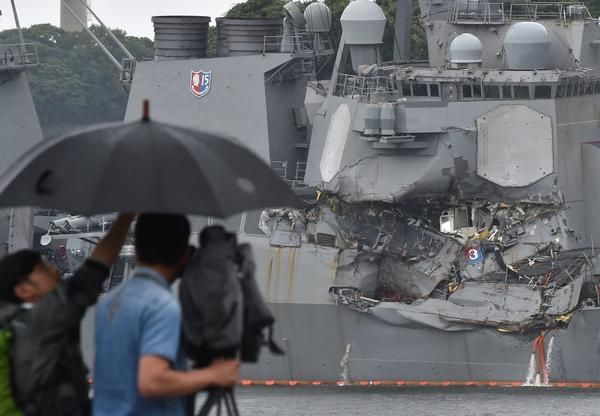 "A TV crew films the damage to the USS Fitzgerald at its port in Yokosuka, Japan, on Sunday. ""A number"" of missing American sailors have been found dead in flooded areas of the destroyer, the U.S. Navy says."