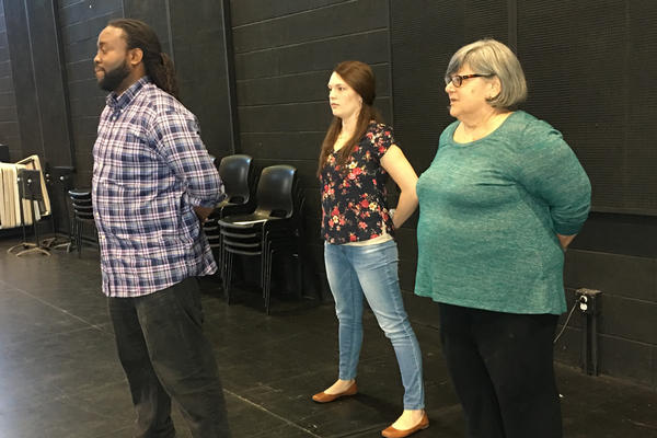 Kendrick Dial, an actor and military veteran, instructs Julia Cuppy (left) and Shirley Fishman on how to assume a proper military posture.