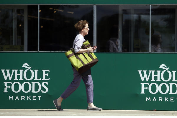A shopper leaves a Whole Foods Market in Northbrook, Ill., Saturday, June 17, 2017. Amazon is buying Whole Foods in a deal valued at about $13.7 billion, a strong move to expand its growing reach into groceries. (Nam Y. Huh/AP)