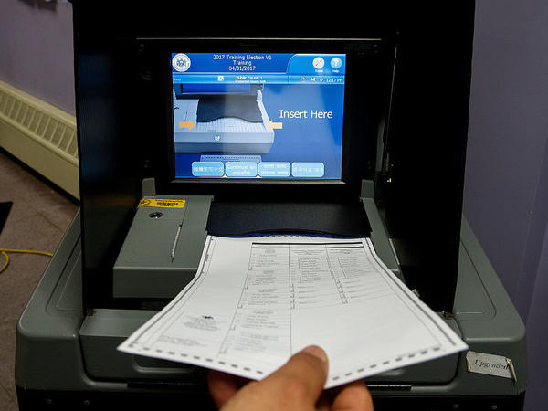 A New York City election worker tests a ballot scanner ahead of the November 2016 election. Two congressional panels are looking into the extent of Russian attempts to hack parts of the election system.