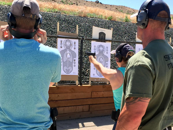 Marty Garland, right, FASTER instructor, looks on as Kelly Blake, a teacher, practices her shooting accuracy.