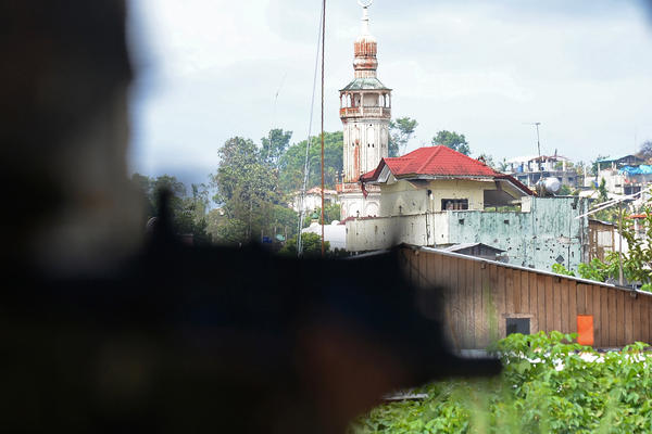 A Philippine soldier scans the cityscape near the front line of the fight in Marawi.