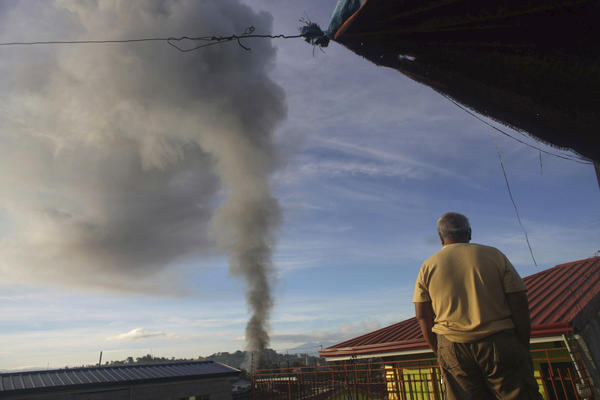 A man looks on during government airstrikes in the early morning Friday in Marawi. Residents had a brief respite from the fighting Sunday, but gunfire quickly returned to the city after a cease-fire was lifted.