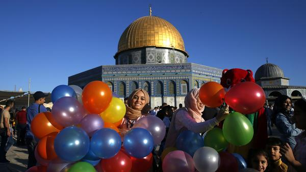 A Palestinian woman holds onto some balloons before the morning Eid al-Fitr prayer near the Dome of Rock in Jerusalem.