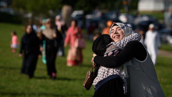 Aya Attal, 17, hugs a friend at an Eid al-Fitr celebration in a park in Pittsburgh, Pa.