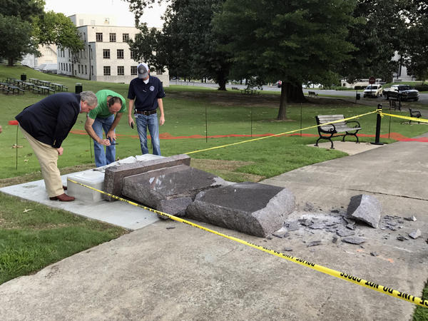 Staff at the Secretary of State's Office inspect the damage to the new Ten Commandments monument outside the state Capitol in Little Rock, Ark., on Wednesday morning. Police say a car crashed into it less than 24 hours after it was installed.