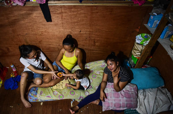 "Baby Roseann plays with her two aunts and mother Rachel Quebec (far right) in their small house. Roseann's father, Clarence Jepadre, 17, was stabbed and killed last year. His body was found with a packet of marijuana and a note saying, ""I'm a pusher... Don't be like me."""